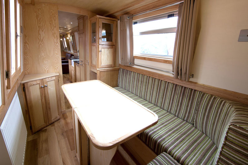 L-shaped dinette on a narrow boat can be used as a seating area; dining and coverts to a double bed