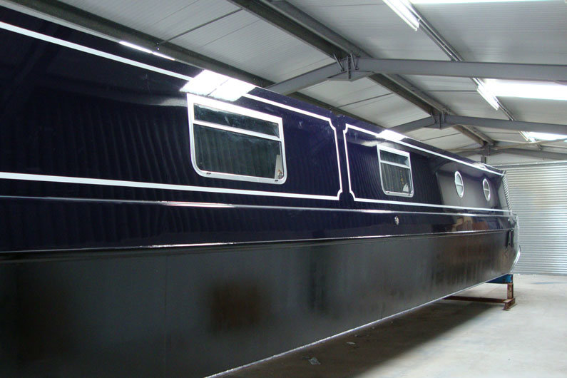 A newly 'blacked' narrowboat hull ready for launch
