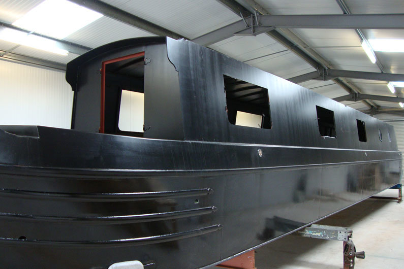Window apertures laser cut in to the narrowboat hull in preparation for windows and portholes to be fitted