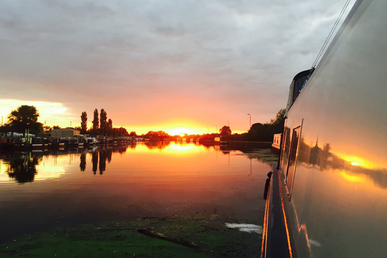 Glorious sunset viewed from a narrowboat on a UK canal