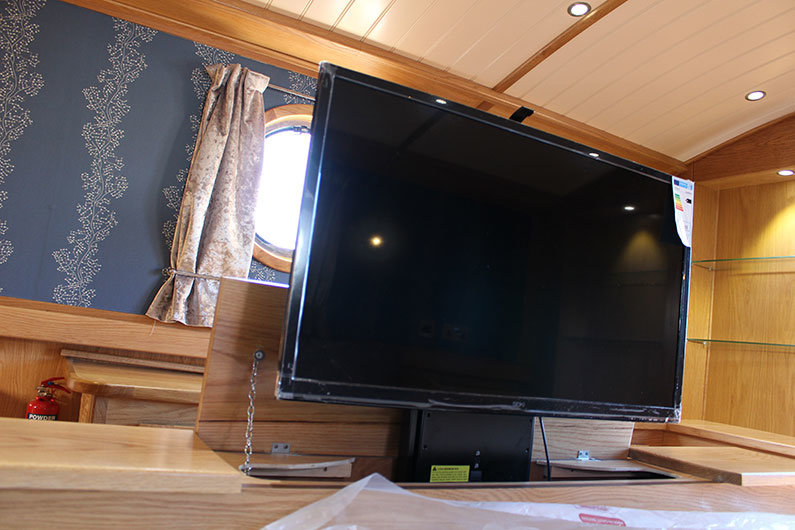 A discreet TV is concealed in the foot of a bed on a narrowboat