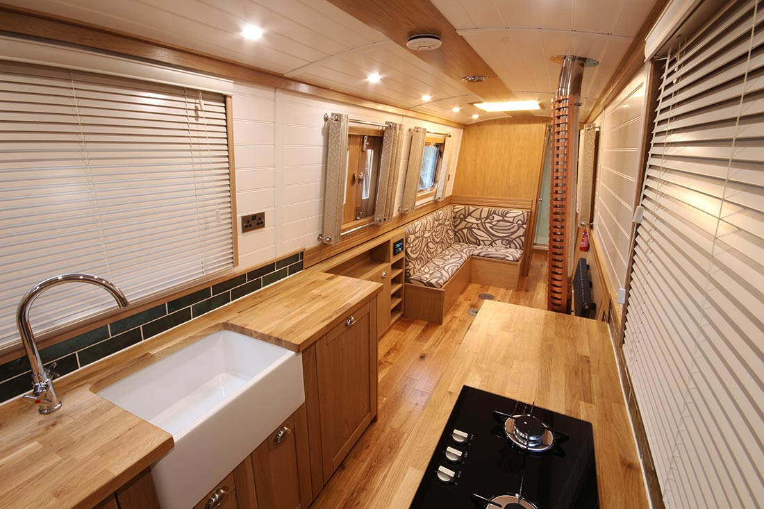 Dinette on narrowboat with table stored discretely behind the cushions for easy access